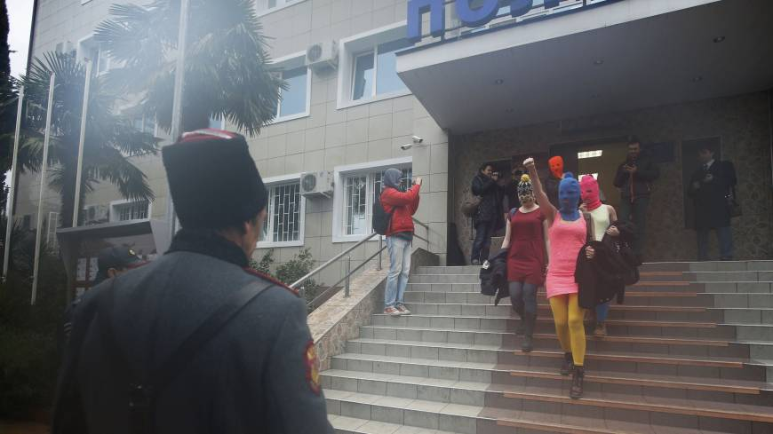 Masked members of Pussy Riot leave a police station Tuesday in Adler. Pussy Riot band members Maria Alyokhina and Nadezhda Tolokonnikova were released from police custody, Tolokonnikova's husband said hours after they were detained in Sochi.