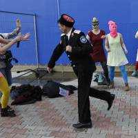 A Cossack militiaman attacks Nadezhda Tolokonnikova and a photographer as she and fellow members of the punk group Pussy Riot, including Maria Alekhina, center, in the pink balaclava, stage a protest performance in Sochi, Russia.
