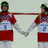 Silver medalist Chloe Dufour-Lapointe (left)  holds hands with her sister and gold medalist Justine Dufour-Lapointe during the award ceremony for the women's freestyle skiing moguls at the Rosa Khutor Extreme Park.