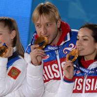 Russian gold medalist Evgeni Plushenko (center) and Julia Lipnitskaia (left) pose with fellow teammates during the medal ceremony for the figure skating team competition on Sunday. | AFP-JIJI