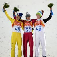 (From left) Noriaki Kasai, Poland's Kamil Stoch and Slovenia's Peter Prevc celebrate on the podium during the flower ceremony for the men's ski jumping large hill individual at the RusSki Gorki Jumping Center. | AFP-JIJI