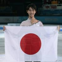 Yuzuru Hanyu poses with Japan's flag after placing first in the men's free skate figure skating final to become the nation's first male athlete to take the Olympics' top prize in figure skating.  | AP