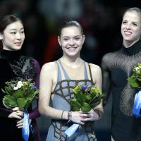 Adelina Sotnikova (center) of Russia,  Yuna Kim (left) of South Korea and Carolina Kostner of Italy stand on the podium during the flower ceremony for the women's  figure skating competition on Thursday. | AP