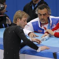 Hometown hero Evgeni Plushenko speaks with his coach Alexei Mishin ( right) and other team members before pulling out of the competition. | AP