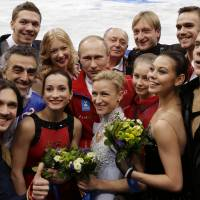 Russian President Vladimir Putin poses with the Russian team after they placed first in the team figure skating competition at the 2014 Winter Olympics, the first gold for the host country. | AP