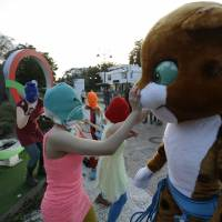 Pussy Riot member Nadezhda Tolokonnikova, in the aqua balaclava, faces off  with an Olympic mascot while the group perform next to the Olympic rings in Sochi, Russia. Earlier in the day, Cossack militia attacked the group with horsewhips.