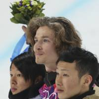 Switzerland's Iouri Podladtchikov, flanked by silver medalist  Ayumu Hirano of Japan (left) and bronze medalist Taku Hiraoka, celebrates on the podium after winning the gold medal in men's snowboard halfpipe final. | AP