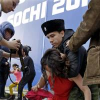 A member of the punk group Pussy Riot is restrained by a member of the Cossack militia Wednesday in Sochi, Russia. | AP