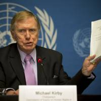 Retired Australian judge Michael Kirby, chairperson of the commission of Inquiry on Human Rights in the Democratic People's Republic of Korea, shows the commission's report during a press conference Monday at the United Nations in Geneva.   AP