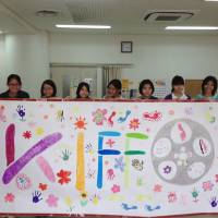 Children involved in the Kinder International Film Festival in Okinawa hold up their design for a special KIFFO opening carpet. | KIFFO