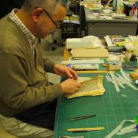 Tipping the scales: Book conservator Setsuo Shinno rescues a damaged book. | KIT NAGAMURA PHOTO