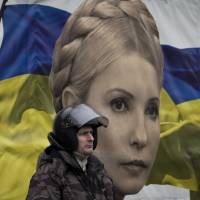 A protester stands in front of a poster of Yulia Tymoshenko in Kiev on Saturday before she was released from prison. | REUTERS