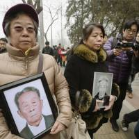 Relatives of Chinese citizens forced into wartime labor for Japanese companies walk to the Beijing No. 1 Intermediate People's Court on Wednesday to file a lawsuit.   KYODO