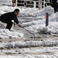 A worker uses a squeegee to push snow from a walkway into a street in Yokohama on Saturday. | AP