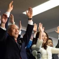 Victory celebration: Yoichi Masuzoe and his wife, Masami, raise their arms and shout 'Banzai!' with supporters at the new Tokyo governor's campaign office Sunday night. | AFP-JIJI