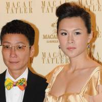Daddy dearest: Gigi Chao (right), the daughter of Hong Kong tycoon Cecil Chao, attends an event with her partner, Sean Eav, in Macau in September 2011. Chao's father has withdrawn a $130 'marriage bounty' he offered only last week to land her a male suitor, after she issued a heartfelt open letter Thursday urging him to accept her sexuality. Chao and Eav have been together for nine years and are reported to have married in 2012 in France. | AFP-JIJI