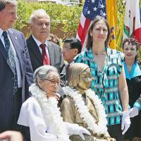 Kim Bok-dong, who spent eight years as a 'comfort women' for the Imperial Japanese Army, sits next to a bronze statue dedicated to the wartime sex slaves at Glendale Central Park near Los Angeles at the memorial's unveiling last July.  | KYODO