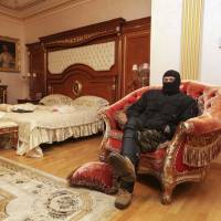 A protester sits in the home of Viktor Pshonka, Ukraine's former prosecutor-general, in the village of Gorenichy on Monday. | REUTERS