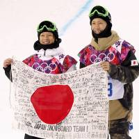 Feeling the love: Halfpipe silver medalist Ayumu Hirano (left) and bronze medalist Taku Hiraoka hold a Hinomaru adorned with messages of support Tuesday in Sochi, Russia. | KYODO