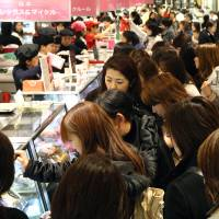 Obligated: Female customers shop for chocolates ahead of Valentine's Day. Japan differs from many countries that celebrate the occasion in that it is women who offer men gifts and not the other way around.   BLOOMBERG