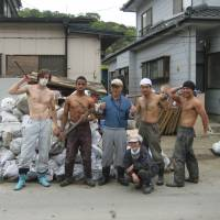 Topless relief: From left to right, volunteers Dean Newcombe, Kris Willis, Nao Noguchi and Tetsuro Hunter pose with a couple of locals in Ishinomaki, Miyagi Prefecture, in 2011. | COURTESY OF INTREPID MODEL ADVENTURES