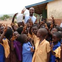 Building hope: Model and actor David Yano, whose NGO, Enije, is working to build a school in Ghana, towers above children on a 2009 trip to the West African country. | GIFTY YANO