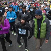 On your marks: Melamed, flanked by supporters, tackles the Tokyo Marathon last Sunday. | NATALIE HOWARD