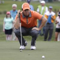 Lie of the land: Rory McIlroy lines up a putt during the first round of the Honda Classic on Thursday. | AP
