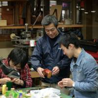 Handing down skills: Katsuhiko Nakano teaches two students how to hand stitch a leather pouch at a workshop in his Asakusa studio. | CAMERON ALLAN MCKEAN
