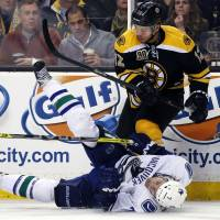 Rough and tumble: Boston's Jarome Iginla dumps Vancouver's David Booth to the ice during the Bruins' 3-1 win on Tuesday. | AP