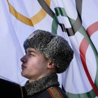 Proud people: A member of a Russian honor guard listens to the Olympic anthem during a welcome ceremony for the German Olympic team at the Mountain Olympic Village prior to the 2014 Winter Olympics on Wednesday in Krasnaya Polyana, Russia. | AP