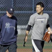 Let's work: Yankees pitcher Masahiro Tanaka walks with pitching coach Larry Rothschild during practice in Tampa, Florida, on Thursday. | AP