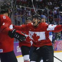 Show some love: Canada's John Tavares prepares to hug teammate Drew Doughty following Doughty's overtime goal against Finland on Sunday in Sochi, Russia. | AP