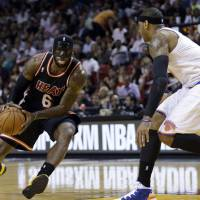 Man in the mask: Miami's LeBron James drives as New York's Carmelo Anthony defends during the Heat's 108-82 win on Thursday. | AP