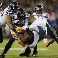 On the defensive: Seahawks defenders K.J. Wright (left), Bobby Wagner (center) and Mike Morgan come together to tackle Broncos receiver Demaryius Thomas during Super Bowl XLVIII on Sunday. Seattle won 43-8. | AP