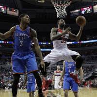 Silencing the Thunder: Washington's Trevor Booker (right) shoots as Oklahoma City's Perry Jones looks on during the Wizards' 96-81 win on Saturday.   AP
