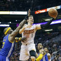 Father figure: Phoenix's Goran Dragic drives past Golden State's Jermaine O'Neal (left) during the Suns' 122-109 win over the Warriors on Saturday. | AP