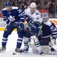 Tight squeeze: Toronto's Carl Gunnarsson (left) battles for the puck with Vancouver's Alexandre Burrows on Saturday.   AP