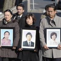 Relatives of three bank employees killed by the March 11, 2011, tsunami hold photos of their loved ones as they enter the Sendai District Court on Tuesday.  | KYODO