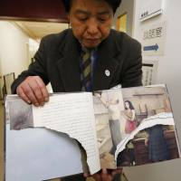 A librarian in Tokyo's Suginami Ward holds a vandalized copy of Anne Frank's 'A Diary of a Young Girl' on Wednesday.   KYODO