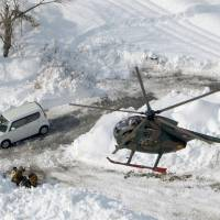 A Ground Self-Defense Force chopper hovers Tuesday over an area in Yamanashi Prefecture where access has been cut off by heavy snow. | KYODO