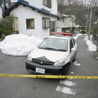 Off-limits: A police officer stands watch near the scene where a man allegedly stabbed a 17-year-old girl to death in Hachioji, Tokyo, on Thursday.   KYODO