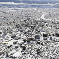 Paint it white: Snow covers the cityscape of Kofu, the capital of Yamanashi Prefecture, on Saturday after a record amount of snow fell in the area overnight. | KYODO