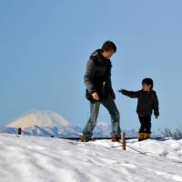 Winter stroll: A boy and his father walk across a snow-covered field in Tokyo on Sunday, with Mount Fuji in the background. | AFP-JIJI
