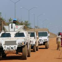 On a mission: Ground Self-Defense Force vehicles under a U.N. peacekeeping mission pass South Sudanese refugees in Juba on Wednesday.   KYODO