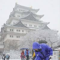 Weather woes: A man shovels snow at Nagoya Castle on Saturday morning. | KYODO