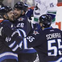 Bring it in: The Jets' Devin Setoguchi (left) celebrates with teammates Blake Wheeler (26) and Mark Scheifele after scoring in the third period against the Canucks on Friday in Winnipeg. The Jets beat Vancouver 4-3. | AP