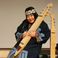 Ainu dance performer Ayaka Ono holds the stringed 'tonkori,' one of the indigenous ethnic group's traditional musical instruments. | KYODO