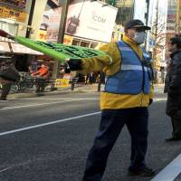 Ever alert: A guard watches over the vehicle-free promenade in Tokyo's Akihabara district on Jan. 12. | YOSHIAKI MIURA