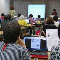Volunteers take an information technology course Nov. 30 in Tokyo on how to make audiobooks for visually impaired people. | KYODO